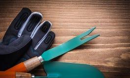 Βοτάνισμα των προστατευτικών γαντιών φτυαριών χεριών σεσουλών στον ξύλινο πίνακα Στοκ Φωτογραφίες