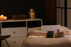 Βοτανικές συμπιέσεις και πέτρες στον πίνακα μασάζ στο σαλόνι SPA στοκ φωτογραφία
