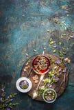 Βοτανική προετοιμασία τσαγιού με τα φρέσκα χορτάρια και τα λουλούδια θεραπείας στο σκοτεινό αγροτικό υπόβαθρο στοκ εικόνες