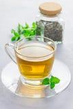 Βοτανικό τσάι μεντών στο φλυτζάνι γυαλιού με το ξηρό peppermint τσάι στο υπόβαθρο, κάθετο Στοκ Εικόνες