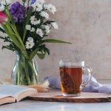 Βοτανικό τσάι με το θυμάρι στο άσπρο υπόβαθρο με την ανθοδέσμη των λουλουδιών και του βιβλίου Στοκ φωτογραφία με δικαίωμα ελεύθερης χρήσης
