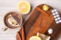 Βοτανικό τσάι με το λεμόνι και τα χάπια όντας χέρι έννοιας έχει το πρόσφατο χάπι οδηγιών υγειονομικής περίθαλψης Στοκ Εικόνες