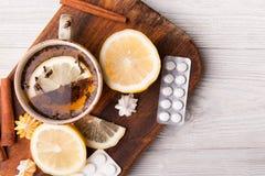 Βοτανικό τσάι με το λεμόνι και τα χάπια όντας χέρι έννοιας έχει το πρόσφατο χάπι οδηγιών υγειονομικής περίθαλψης Στοκ Φωτογραφίες