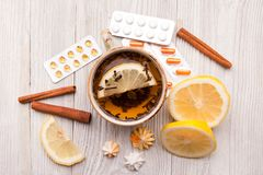 Βοτανικό τσάι με το λεμόνι και τα χάπια όντας χέρι έννοιας έχει το πρόσφατο χάπι οδηγιών υγειονομικής περίθαλψης Στοκ Εικόνα