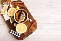 Βοτανικό τσάι με το λεμόνι και τα χάπια όντας χέρι έννοιας έχει το πρόσφατο χάπι οδηγιών υγειονομικής περίθαλψης Στοκ εικόνα με δικαίωμα ελεύθερης χρήσης