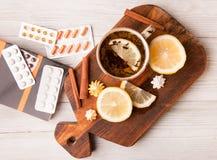 Βοτανικό τσάι με το λεμόνι και τα χάπια όντας χέρι έννοιας έχει το πρόσφατο χάπι οδηγιών υγειονομικής περίθαλψης Στοκ Φωτογραφία