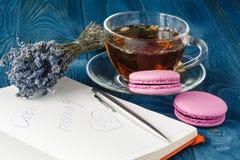 Βοτανικό τσάι σε ένα διαφανές φλυτζάνι γυαλιού και ένα ανοικτό καθαρό σημειωματάριο Στοκ φωτογραφία με δικαίωμα ελεύθερης χρήσης
