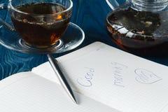 Βοτανικό τσάι σε ένα διαφανές φλυτζάνι γυαλιού και ένα ανοικτό καθαρό σημειωματάριο Στοκ Φωτογραφίες