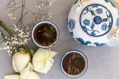 Βοτανικό τσάι στα εκλεκτής ποιότητας φλυτζάνια και τα τριαντάφυλλα Στοκ Φωτογραφίες