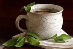 Βοτανικό τσάι στα φύλλα κεραμικών φλυτζανιών και salvia στο σκοτεινό καφετί ξύλο Στοκ Εικόνες