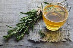 Βοτανικό τσάι της Rosemary σε ένα φλυτζάνι γυαλιού με το φρέσκο πράσινο χορτάρι δεντρολιβάνου στο αγροτικό ξύλινο υπόβαθρο στοκ εικόνα με δικαίωμα ελεύθερης χρήσης