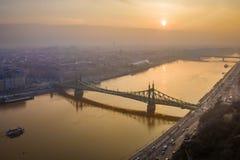 Βουδαπέστη, Ουγγαρία - η εναέρια άποψη της γέφυρας Szabadsag ελευθερίας έκρυψε πέρα από τον ποταμό Δούναβης στην ανατολή Στοκ Εικόνα