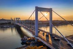 Βουδαπέστη, Ουγγαρία - η όμορφη γέφυρα Erzsebet της Elisabeth έκρυψε στην ανατολή με χρυσό και το μπλε ουρανό, βαριά κυκλοφορία π στοκ φωτογραφία με δικαίωμα ελεύθερης χρήσης