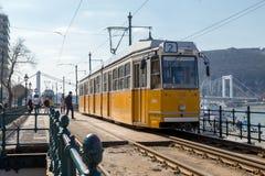 Βουδαπέστη, Ουγγαρία, στις 22 Μαρτίου 2018: Κίτρινο τραμ τον πρώιμο χειμώνα με το νεφελώδη ουρανό Το τραμ αριθμός 2 είναι διάσημο Στοκ φωτογραφίες με δικαίωμα ελεύθερης χρήσης