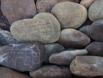 Βουδιστικές πέτρες προσευχής: στον ποταμό οι στρογγυλευμένοι λίθοι είναι χρωματισμένα αρχαία θιβετιανά mantras σε σανσκριτικό Στοκ εικόνες με δικαίωμα ελεύθερης χρήσης