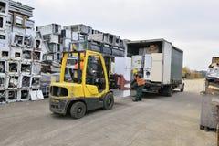 Βουκουρέστι, Ρουμανία - τον Οκτώβριο του 2013: Εργαζόμενοι που ταξινομούν τα ηλεκτρονικά απόβλητα από ένα πρόσφατα προσεγγισμένο  στοκ φωτογραφίες