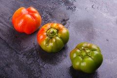 Βουλγαρικό πιπέρι, πορτοκαλής και πράσινος, σε ένα μαύρο υπόβαθρο Στοκ Εικόνες