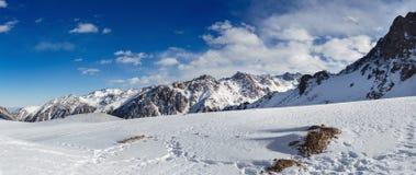 Βουνά κάτω από το χιόνι το χειμώνα Πανόραμα του τοπίου σειράς βουνών χιονιού Στοκ Φωτογραφία
