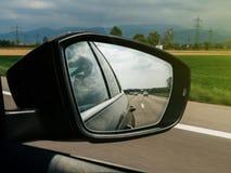 Βουνά και αυτοκίνητα και εθνική οδός που βλέπουν στον οπισθοσκόπο καθρέφτη του α Στοκ Εικόνες