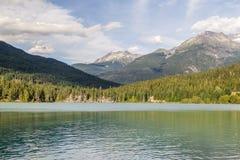 Βουνά και πράσινη λίμνη κοντά στο συριστήρα Καναδάς Στοκ Εικόνα