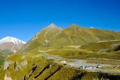 Βουνά Καύκασου το καλοκαίρι, τους πράσινους λόφους, το μπλε ουρανό και χιονώδες μέγιστο Mkinvari δρόμος από Gudauri σε Stepantsmi Στοκ Εικόνες