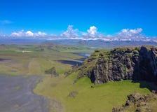 Βουνά που καλύπτονται με το πράσινο βρύο, τη μαύρη παραλία άμμου και τα άσπρα ωκεάνια κύματα στο υπόβαθρο Dyrholaey, νότια Ισλανδ στοκ εικόνα
