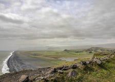 Βουνά που καλύπτονται με το πράσινο βρύο, τη μαύρη παραλία άμμου και τα άσπρα ωκεάνια κύματα στο υπόβαθρο Dyrholaey, νότια Ισλανδ στοκ εικόνες