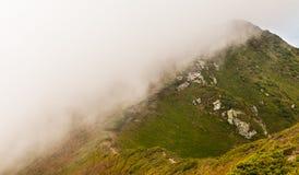 βουνά σύννεφων πέρα από τη θύ&epsilon Στοκ Φωτογραφίες