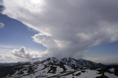 Βουνά την άνοιξη με τα ίχνη χιονιού και εντυπωσιακών σύννεφων Στοκ Φωτογραφίες