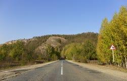 Βουνά φθινοπώρου, το σημάδι δρόμων με πολλ'ες στροφές Στοκ Φωτογραφίες