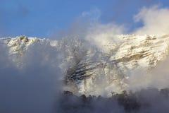Βουνά χιονιού στο ηλιοβασίλεμα με την ομίχλη Στοκ Εικόνες