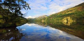 Βουνά Snowdonian και νεφελώδεις μπλε ουρανοί που απεικονίζονται σε ειρηνικό Llyn Gwynant στοκ εικόνες