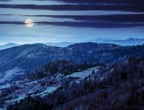 Βουνοπλαγιά φθινοπώρου με τα ζωηρόχρωμα δέντρα φυλλώματος κοντά στην κοιλάδα τη νύχτα Στοκ Εικόνα