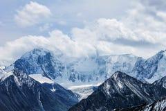 Βουνό που καλύπτεται με το χιόνι, που τυλίγεται στα σύννεφα Στοκ Εικόνες
