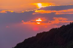 Βουνό στο υπόβαθρο ενός πορτοκαλιού ηλιοβασιλέματος με τα πορφυρά σύννεφα Στοκ Εικόνες