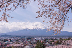 Βουνό Fujiyama, ένα αξιοπρόσεκτο σημάδι εδάφους της Ιαπωνίας σε μια νεφελώδη ημέρα με το άνθος κερασιών ή Sakura στο πλαίσιο Η ει Στοκ Φωτογραφίες