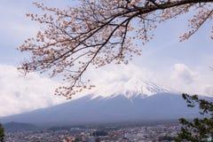 Βουνό Fujiyama, ένα αξιοπρόσεκτο σημάδι εδάφους της Ιαπωνίας σε μια νεφελώδη ημέρα με το άνθος κερασιών ή Sakura στο πλαίσιο Η ει Στοκ φωτογραφία με δικαίωμα ελεύθερης χρήσης