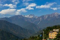 Βουνό Kangchenjunga με τα σύννεφα ανωτέρω και το θερμοκήπιο στεγών Μεταξύ των πράσινων λόφων που βλέπουν το βράδυ στο βόρειο Sikk Στοκ Φωτογραφίες