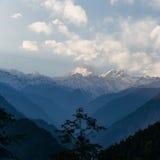 Βουνό Kangchenjunga με τα σύννεφα ανωτέρω Μεταξύ των πράσινων λόφων και των δέντρων που βλέπουν το βράδυ στο βόρειο Sikkim, Ινδία Στοκ Φωτογραφίες