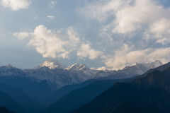 Βουνό Kangchenjunga με τα σύννεφα ανωτέρω Μεταξύ των πράσινων λόφων και των δέντρων που βλέπουν το βράδυ στο βόρειο Sikkim, Ινδία Στοκ Εικόνα