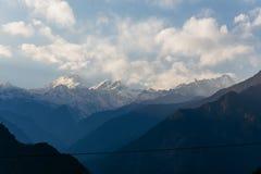 Βουνό Kangchenjunga με τα σύννεφα ανωτέρω Μεταξύ των πράσινων λόφων που βλέπουν το βράδυ στο βόρειο Sikkim, Ινδία Στοκ Εικόνα