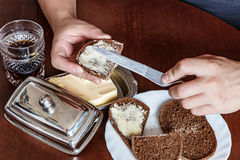 Βουτυρωμένο μαχαίρι ψωμιού ατόμων είναι αριστερόχειρας σούπα, βούτυρο Στοκ φωτογραφίες με δικαίωμα ελεύθερης χρήσης