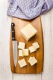 Βουτύρου κύβοι και μαχαίρι κουζινών σε έναν ξύλινο πίνακα Στοκ Φωτογραφίες