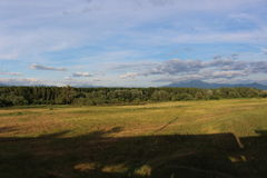 Βουλγαρική φύση - ένας μπλε ουρανός με τα μικρούς σύννεφα, τα δέντρα και τους τομείς στοκ εικόνα