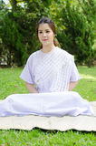 Βουδιστική ταϊλανδική γυναίκα ευχαριστημένη από την άσπρη συνεδρίαση ιματισμού για το medita Στοκ Φωτογραφία