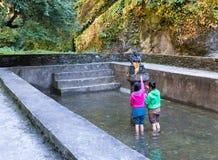 Βουδιστική τελετή δύο η νεπαλική κοριτσιών προσεύχεται το εσωτερικό ιερό waterpool Στοκ Εικόνες
