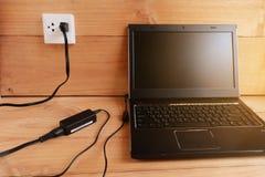 Βούλωμα στο φορτιστή σκοινιού δύναμης προσαρμοστών του φορητού προσωπικού υπολογιστή στο ξύλινο πάτωμα στοκ φωτογραφία με δικαίωμα ελεύθερης χρήσης
