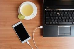 Βούλωμα στο φορτιστή σκοινιού USB του κινητού τηλεφώνου με ένα lap-top και πρόσφατα χυμός ασβέστη σε ένα άσπρο φλυτζάνι, στο ξύλι στοκ εικόνες με δικαίωμα ελεύθερης χρήσης