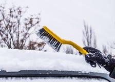 Βούρτσα αυτοκινήτων Καθαρίζοντας αυτοκίνητο από το χιόνι Στοκ εικόνα με δικαίωμα ελεύθερης χρήσης