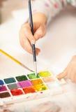 Βούρτσα εκμετάλλευσης κοριτσιών και ζωγραφική με το watercolor Στοκ φωτογραφία με δικαίωμα ελεύθερης χρήσης